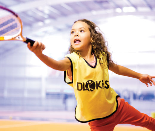 Image of girl hitting tennis ball
